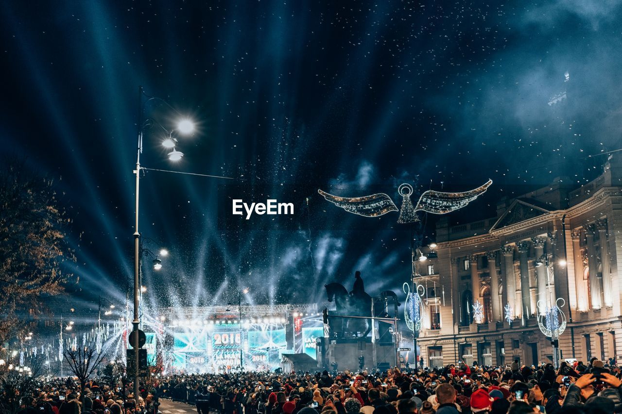 Crowd at music concert against sky at night