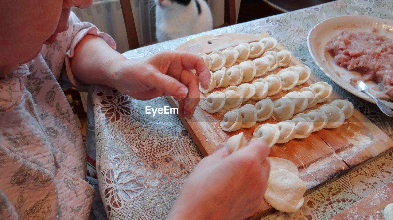 Cropped image of woman preparing dumplings at home