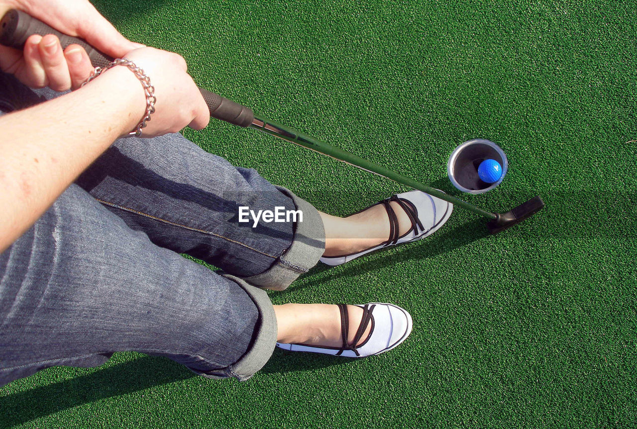 Low Section Of Woman Playing Miniature Golf