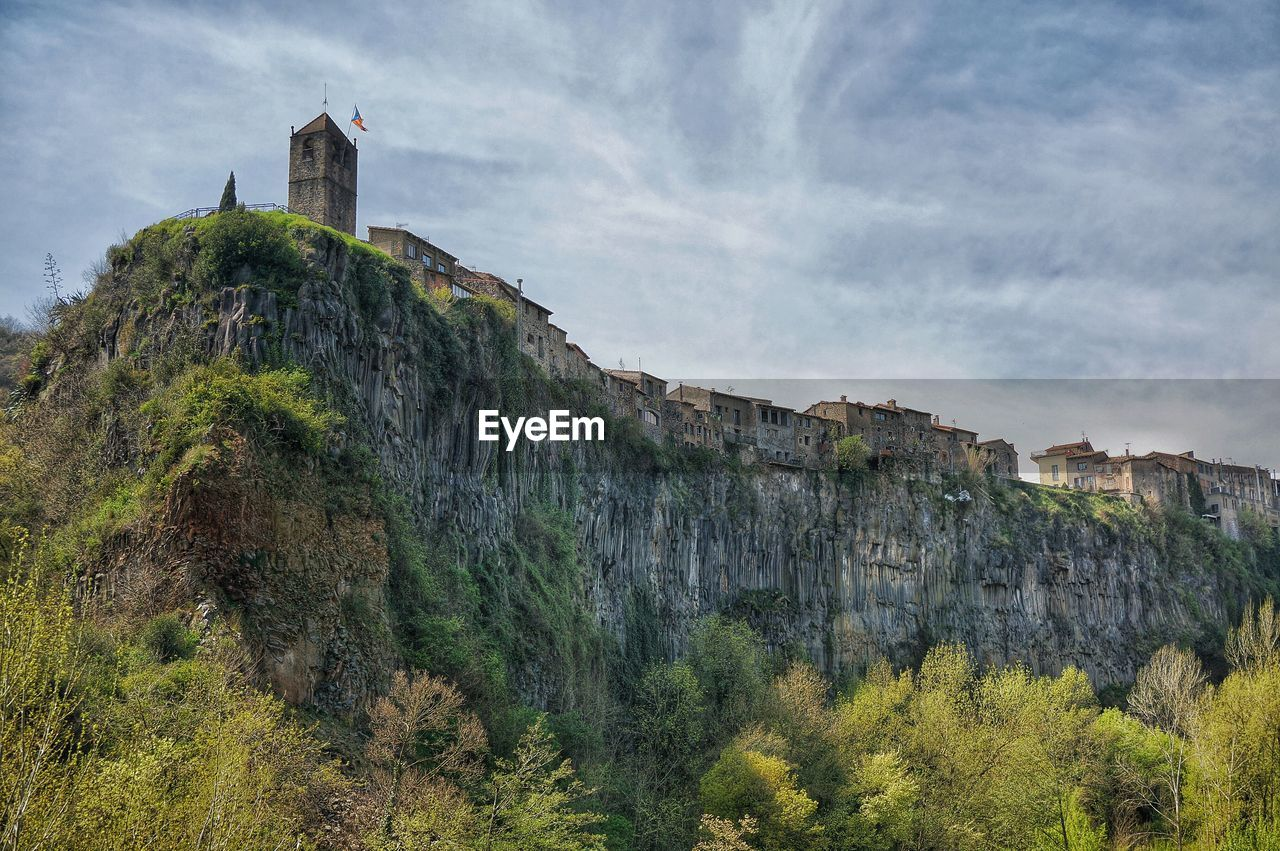 architecture, built structure, building exterior, rock - object, history, cliff, mountain, sky, day, cloud - sky, outdoors, nature, castle, low angle view, no people, tree, beauty in nature