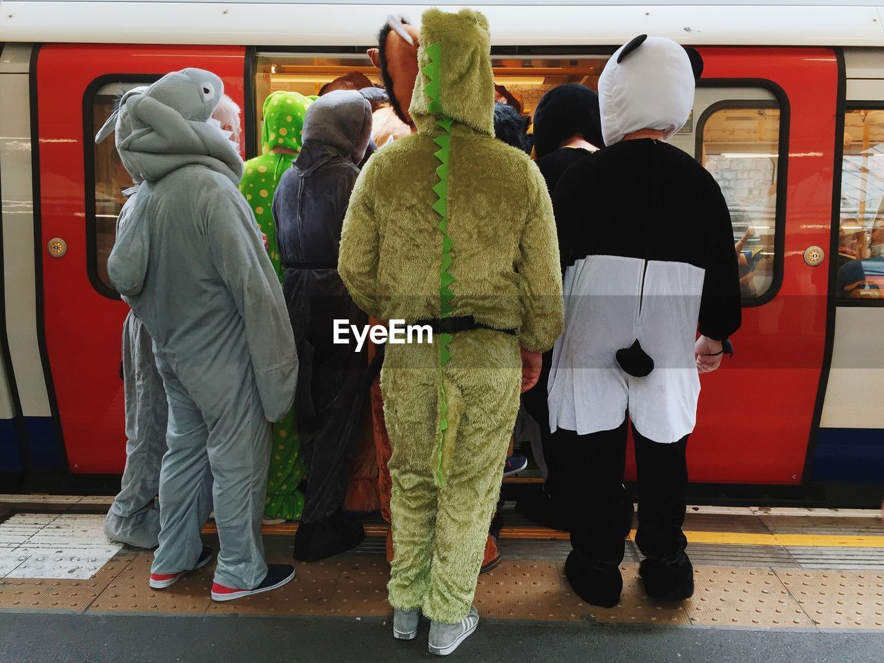 rear view, full length, hood - clothing, real people, hooded shirt, public transportation, transportation, standing, day, childhood, outdoors, men, togetherness, friendship, warm clothing, people