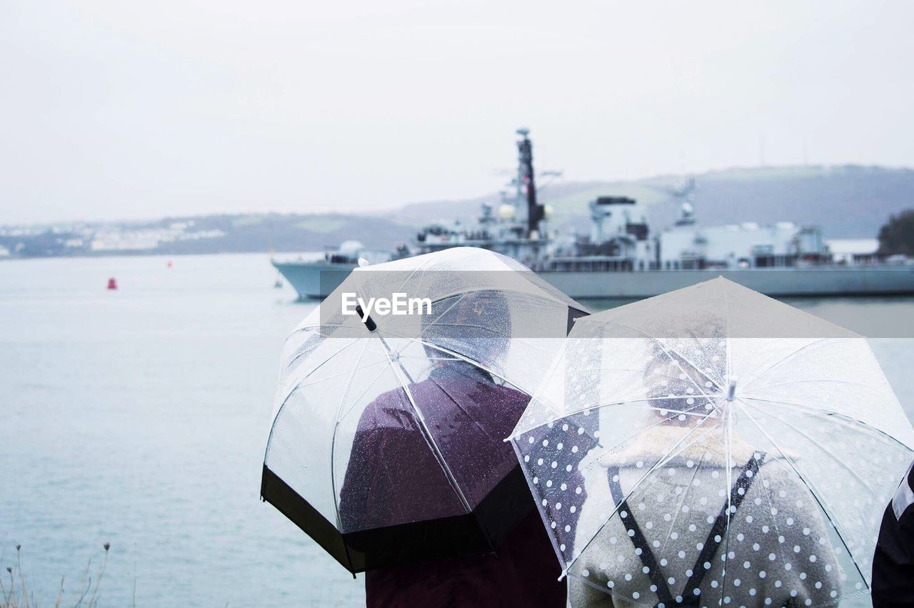 Rear View Of People With Umbrellas Watching Ship