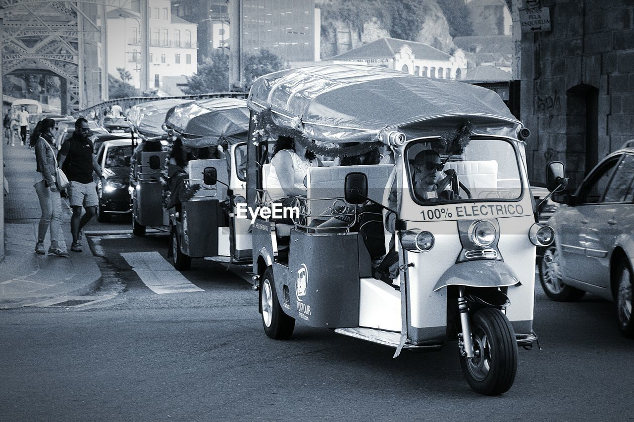 transportation, land vehicle, real people, street, mode of transport, car, city life, city, outdoors, road, day, architecture, building exterior, men, public transportation, built structure, sitting, large group of people, adult, people