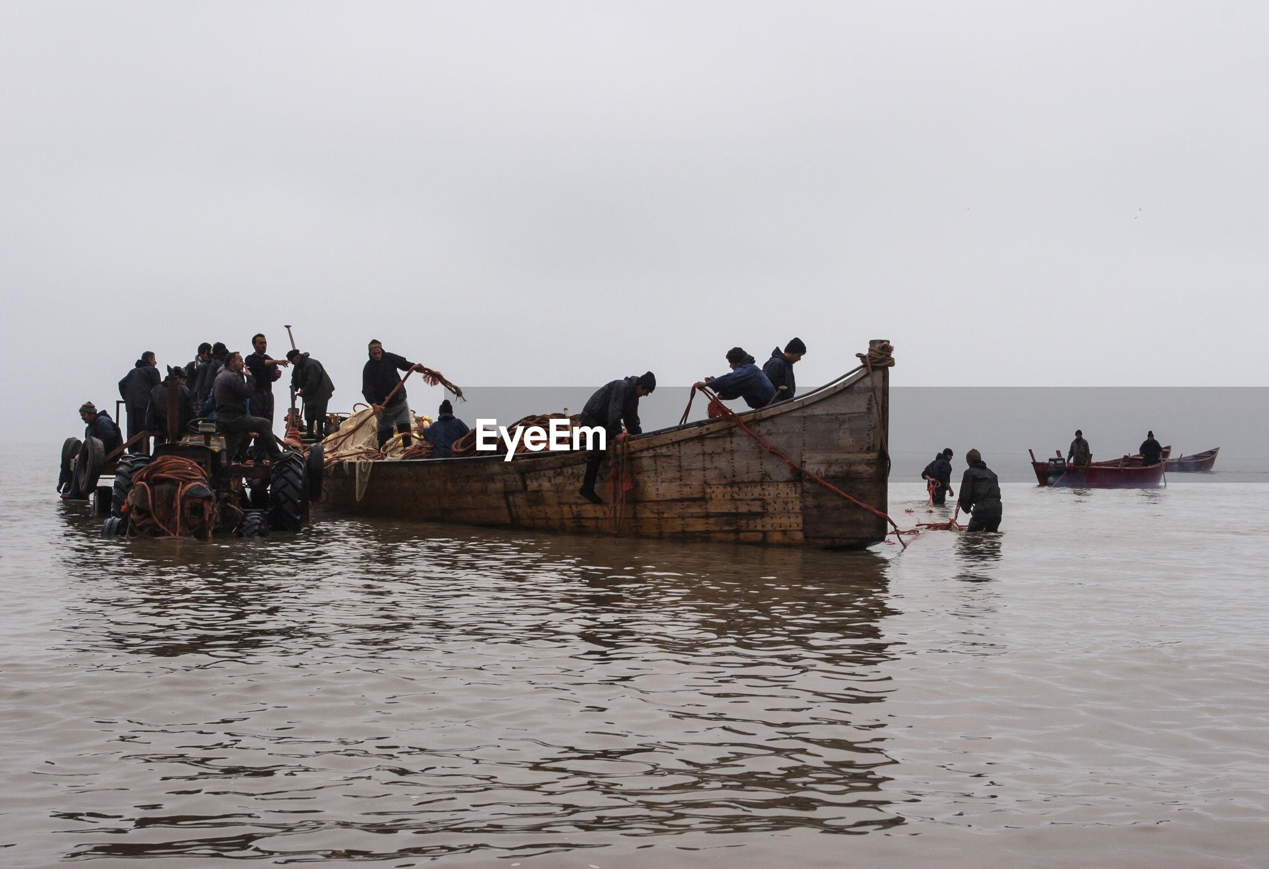 Fishermen fishing in sea against clear sky