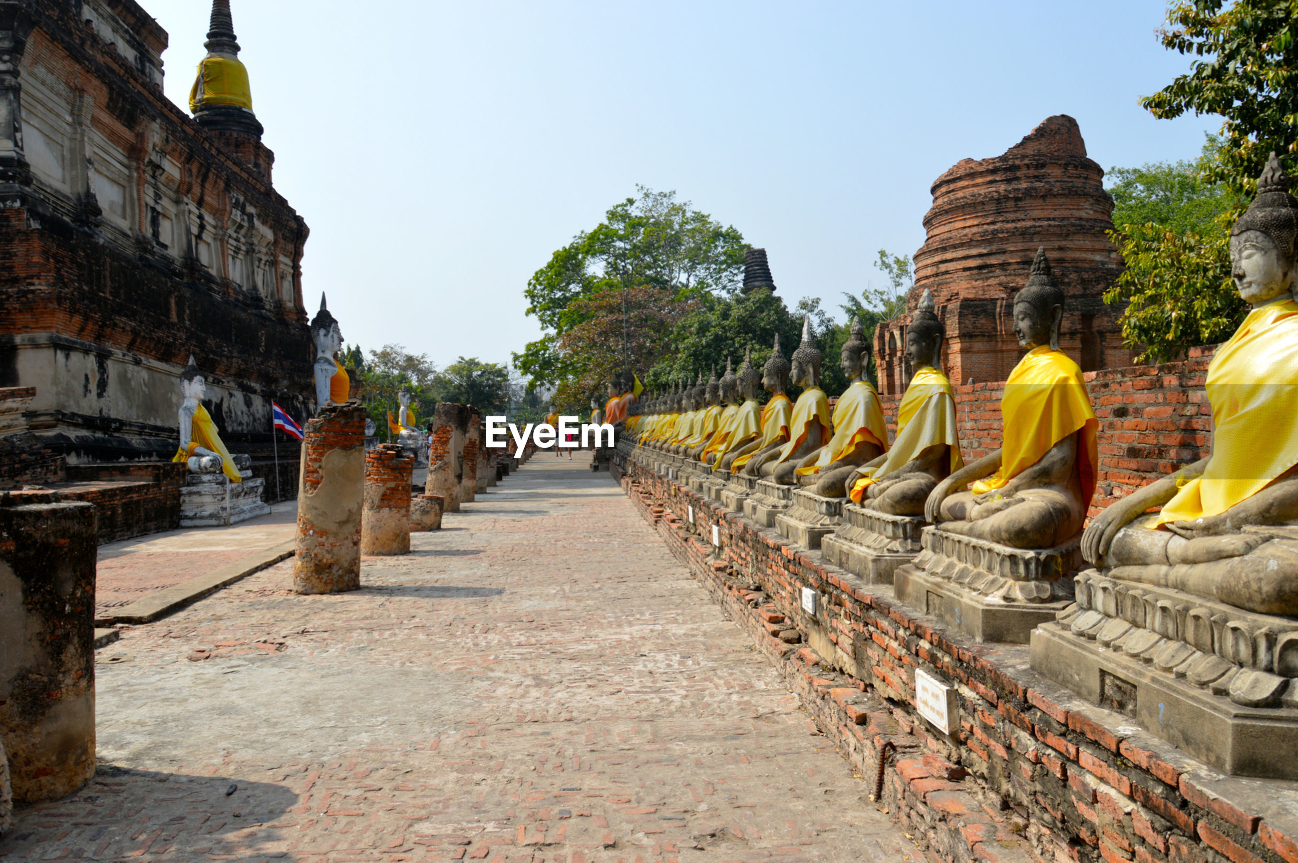 Buddha statues at temple against clear sky