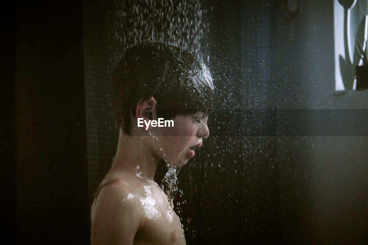 Side View Of Shirtless Boy Showering In Bathroom