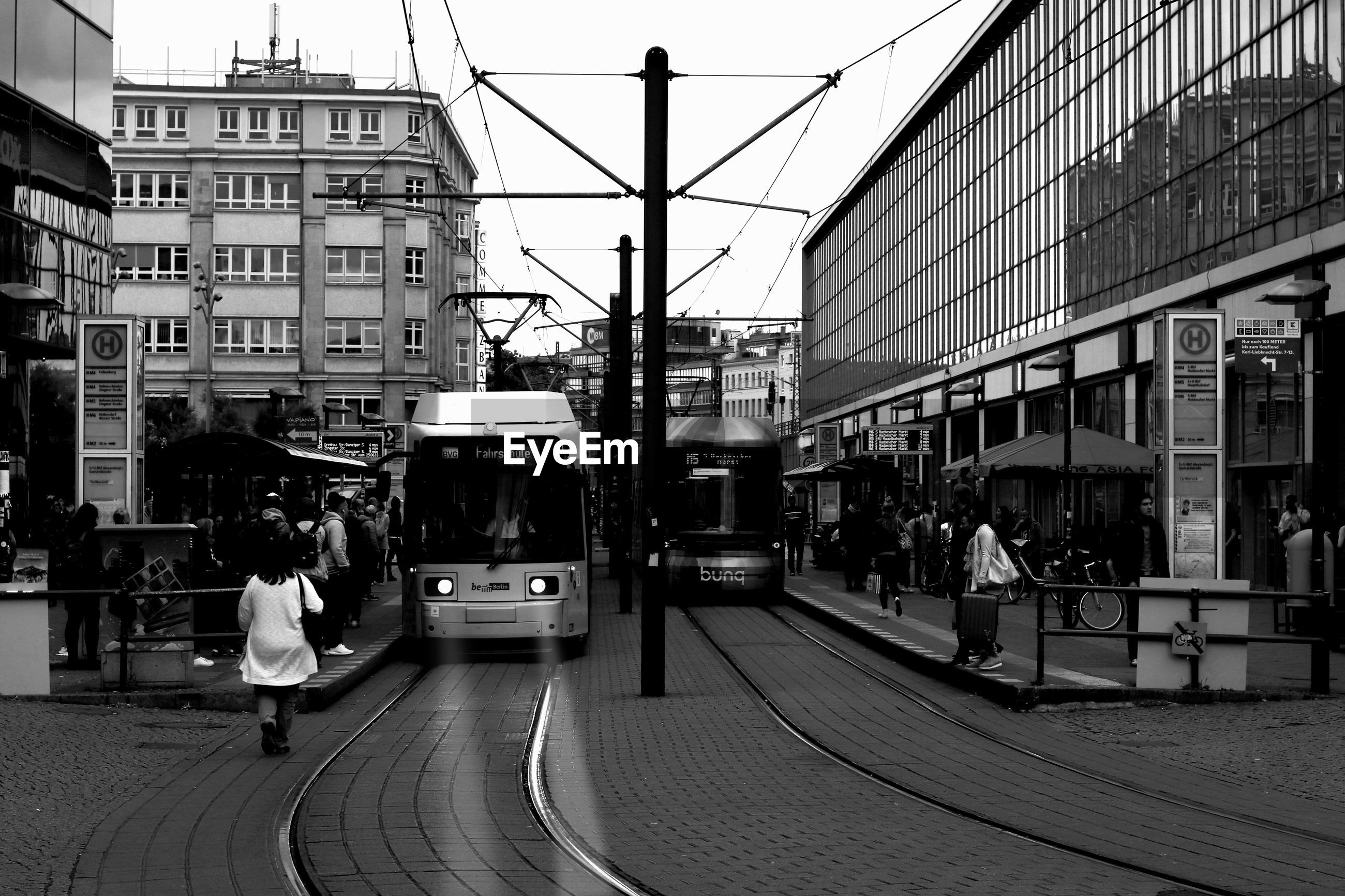 Trams on street amidst buildings in city