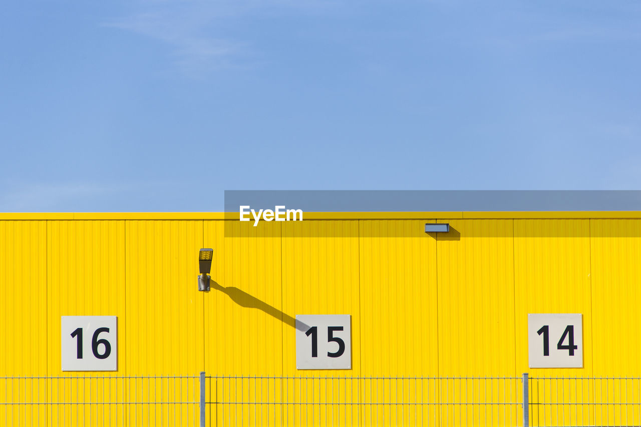 Low Angle View Of Numbers On Yellow Wall Against Sky During Sunny Day