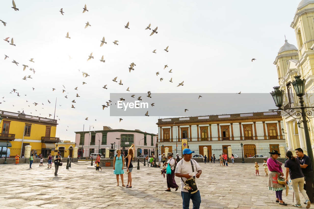 People at town square with birds flying against sky in city