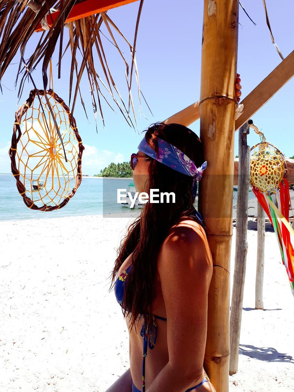 Close-Up Of Woman With Dreamcatcher Standing At Beach Against Sky