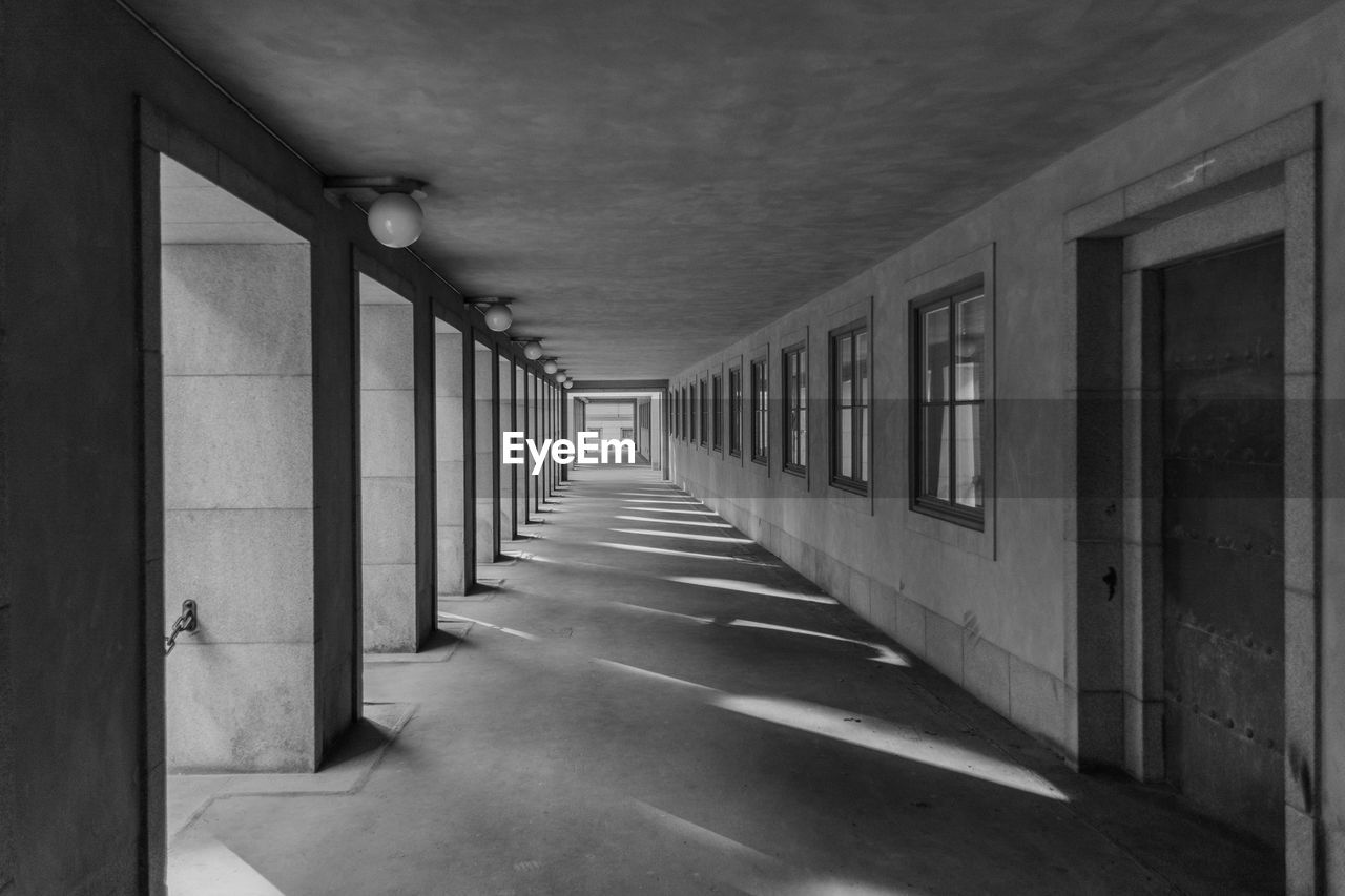 Empty long corridor along wall and pillars