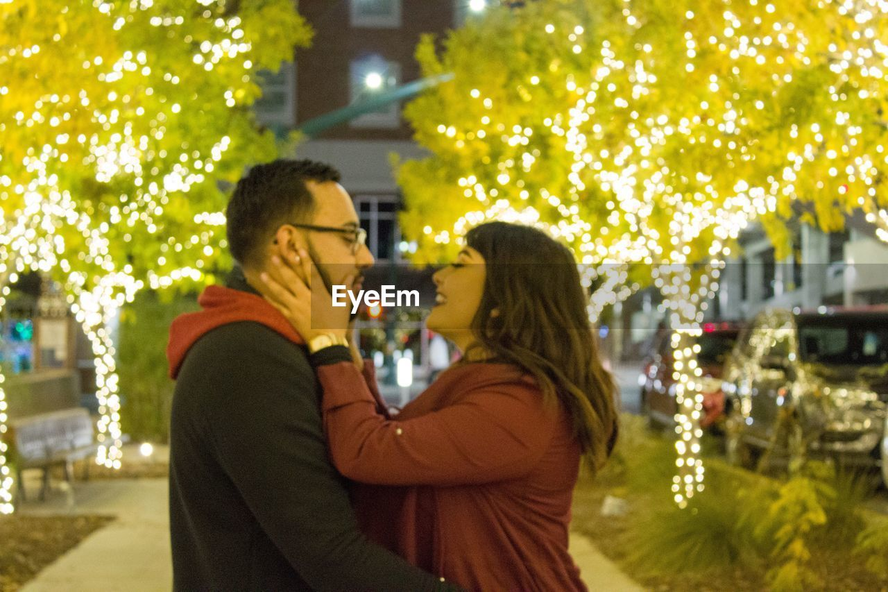 two people, togetherness, love, bonding, women, positive emotion, emotion, adult, night, young adult, real people, tree, leisure activity, plant, young women, side view, waist up, couple - relationship, standing, lifestyles, warm clothing, outdoors, hairstyle