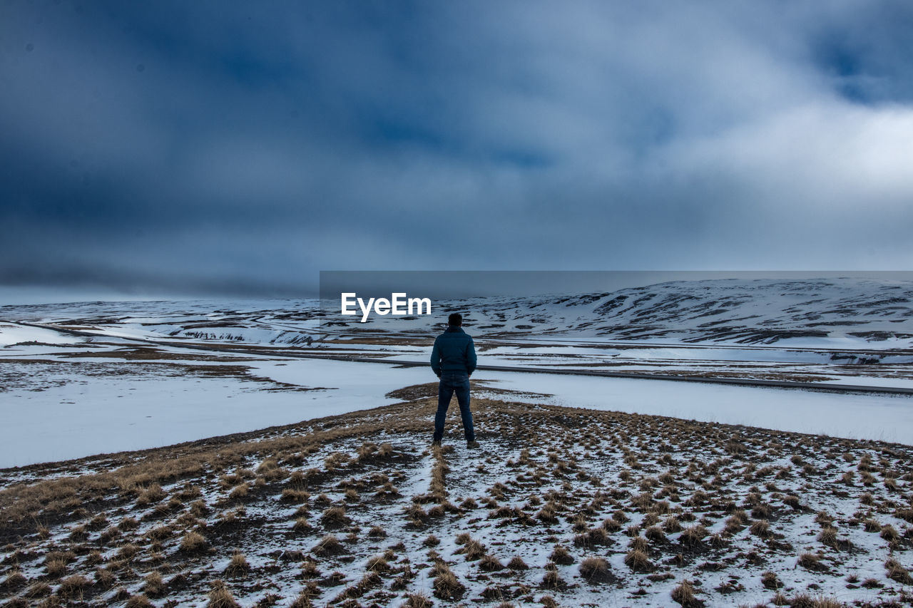 one person, cloud - sky, real people, rear view, sky, water, lifestyles, full length, standing, beauty in nature, nature, land, sea, leisure activity, scenics - nature, day, snow, beach, outdoors, horizon over water, looking at view