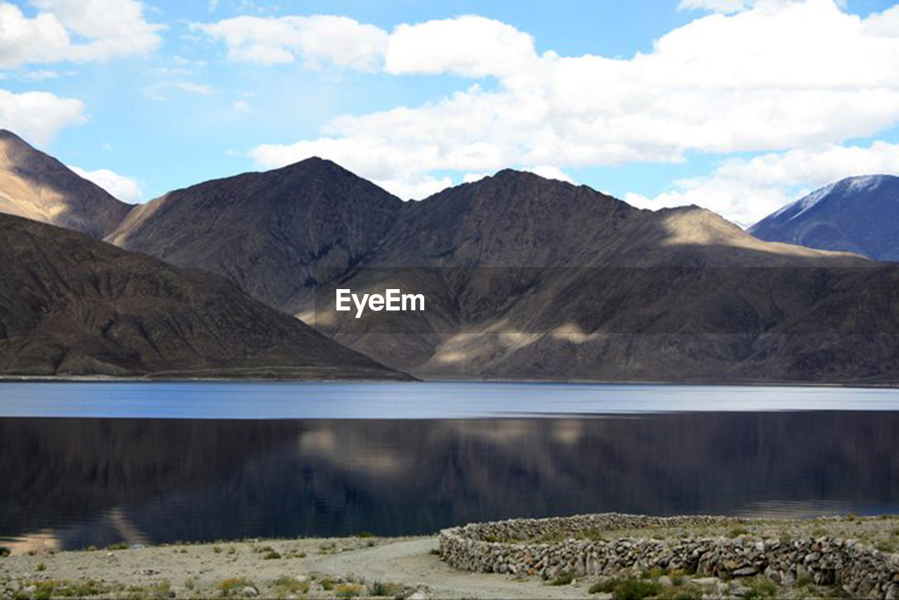 mountain, water, lake, sky, scenics - nature, beauty in nature, mountain range, cloud - sky, nature, tranquil scene, reflection, day, tranquility, environment, landscape, no people, non-urban scene, wilderness, waterfront, mountain peak, outdoors, formation, range