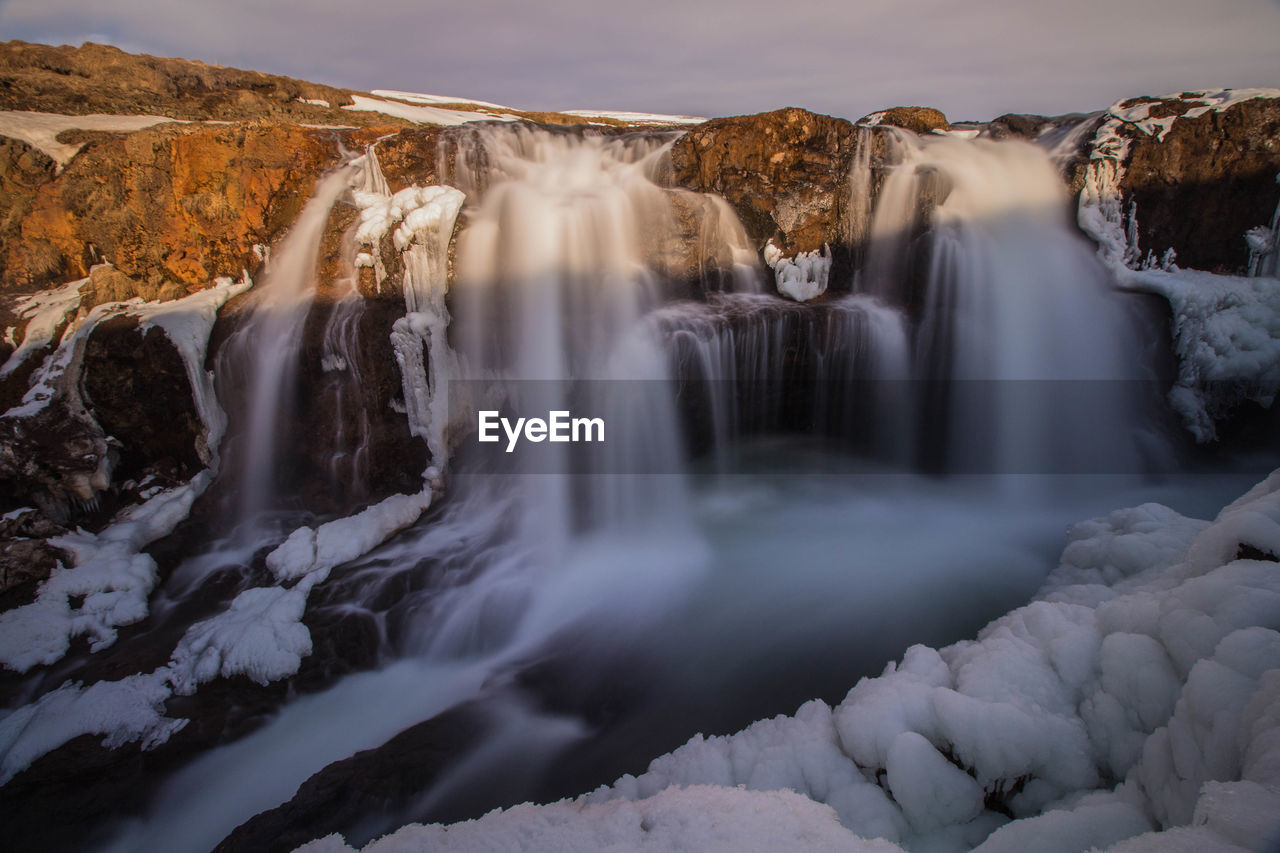 Waterfall falling from mountains in river during winter