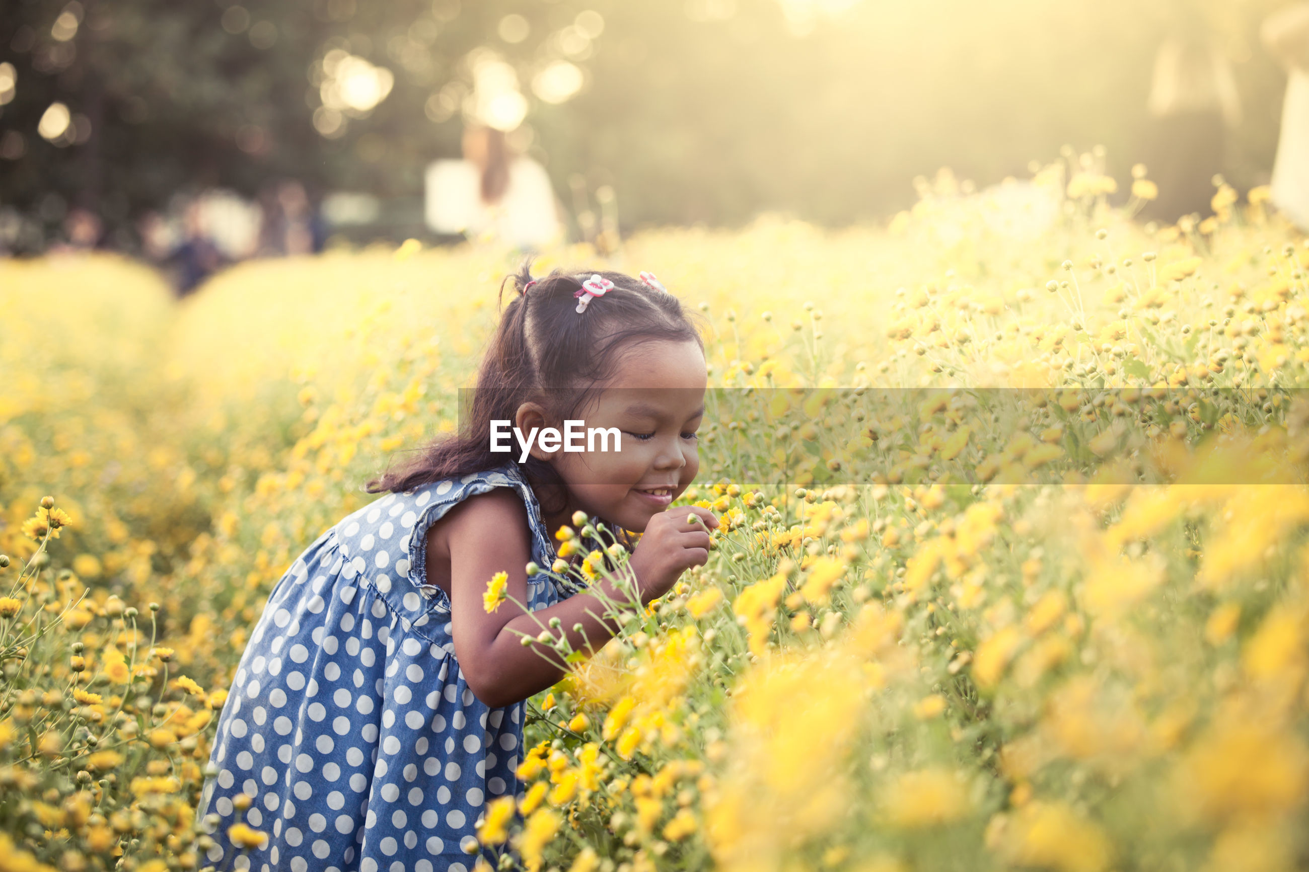 Carefree girl playing with flower on field