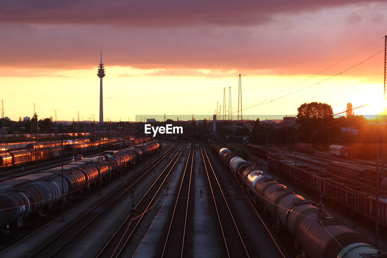 sunset, railroad track, rail transportation, sky, track, transportation, mode of transportation, public transportation, architecture, nature, travel, orange color, built structure, cloud - sky, high angle view, train, railroad station, silhouette, no people, outdoors, electricity, power supply, spire, station