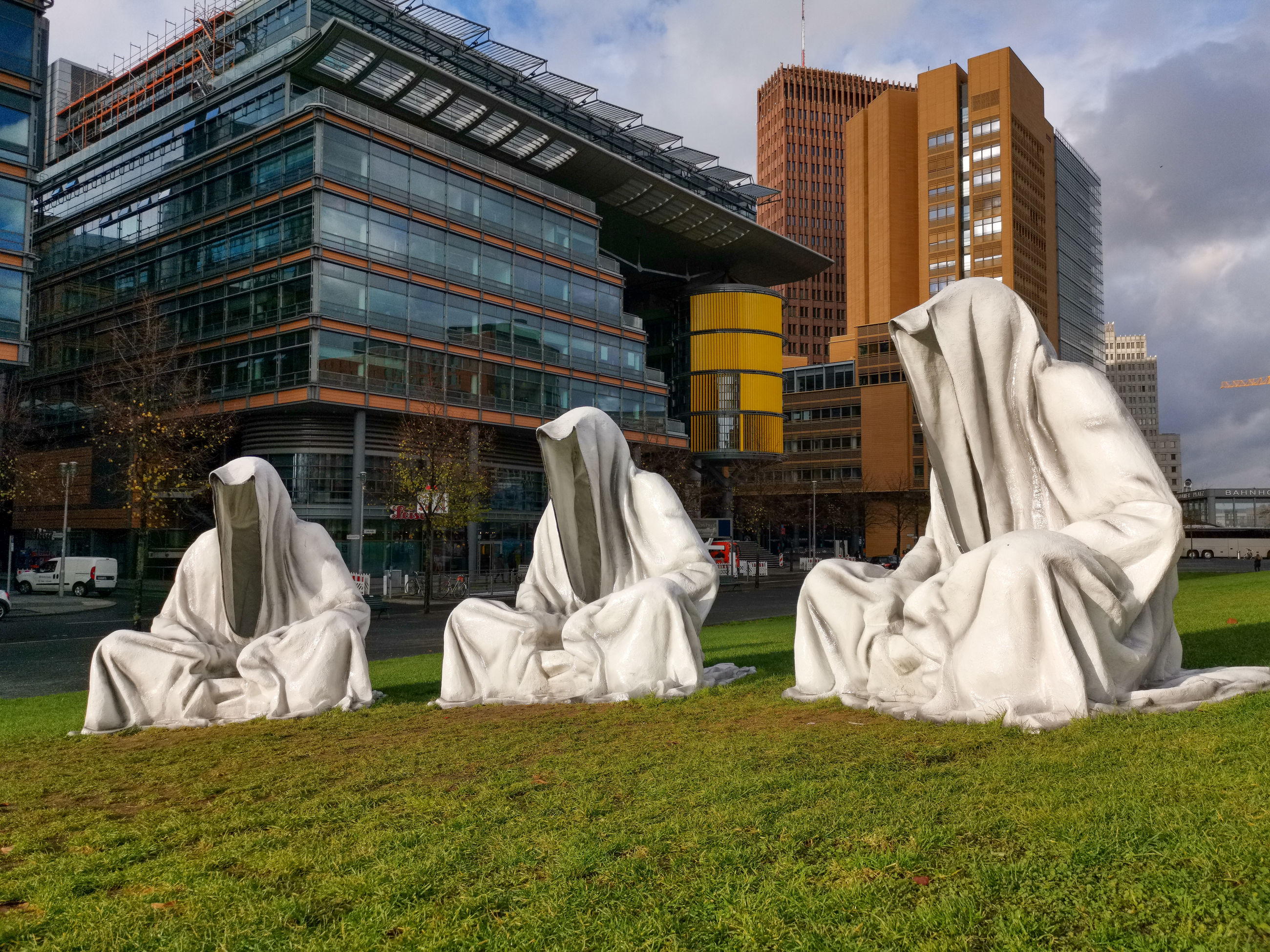 WHITE SCULPTURE ON FIELD BY BUILDINGS AGAINST SKY