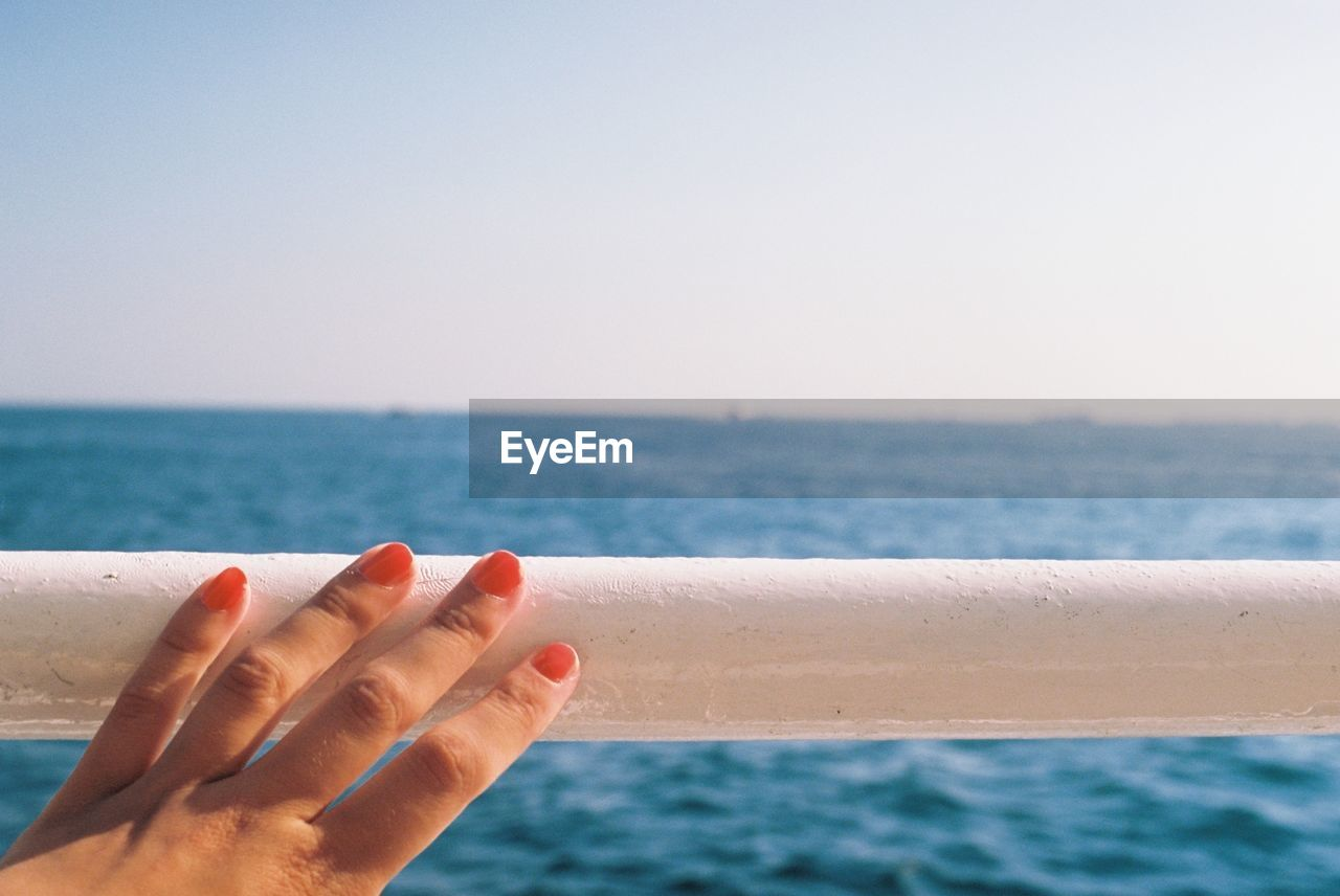 Close-up of hand touching railing against sea