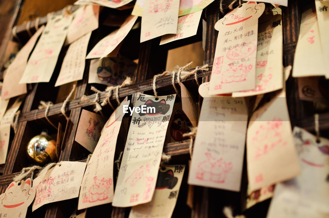 Close-up of papers hanging on railing at shrine