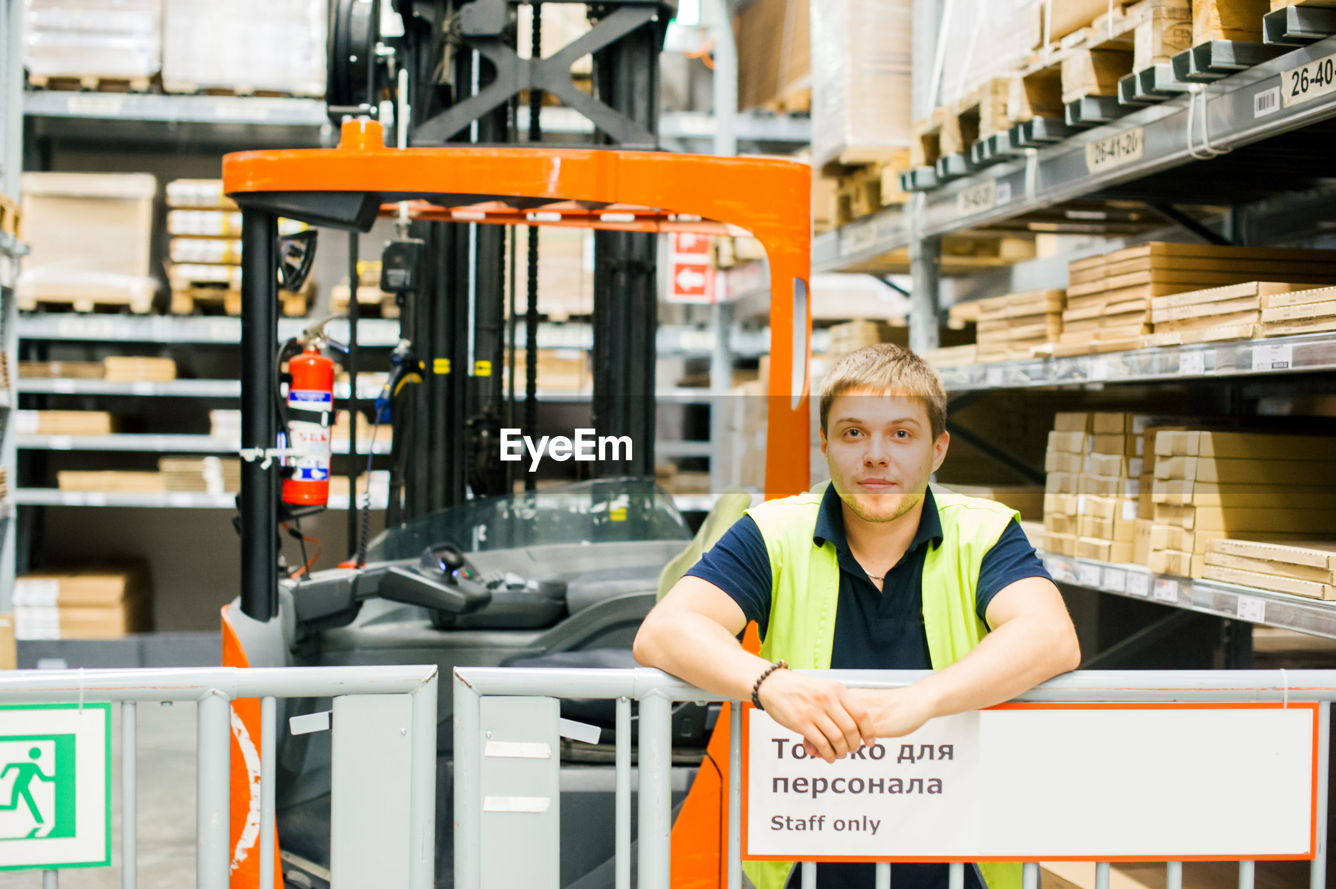 Worker standing by forklift in factory