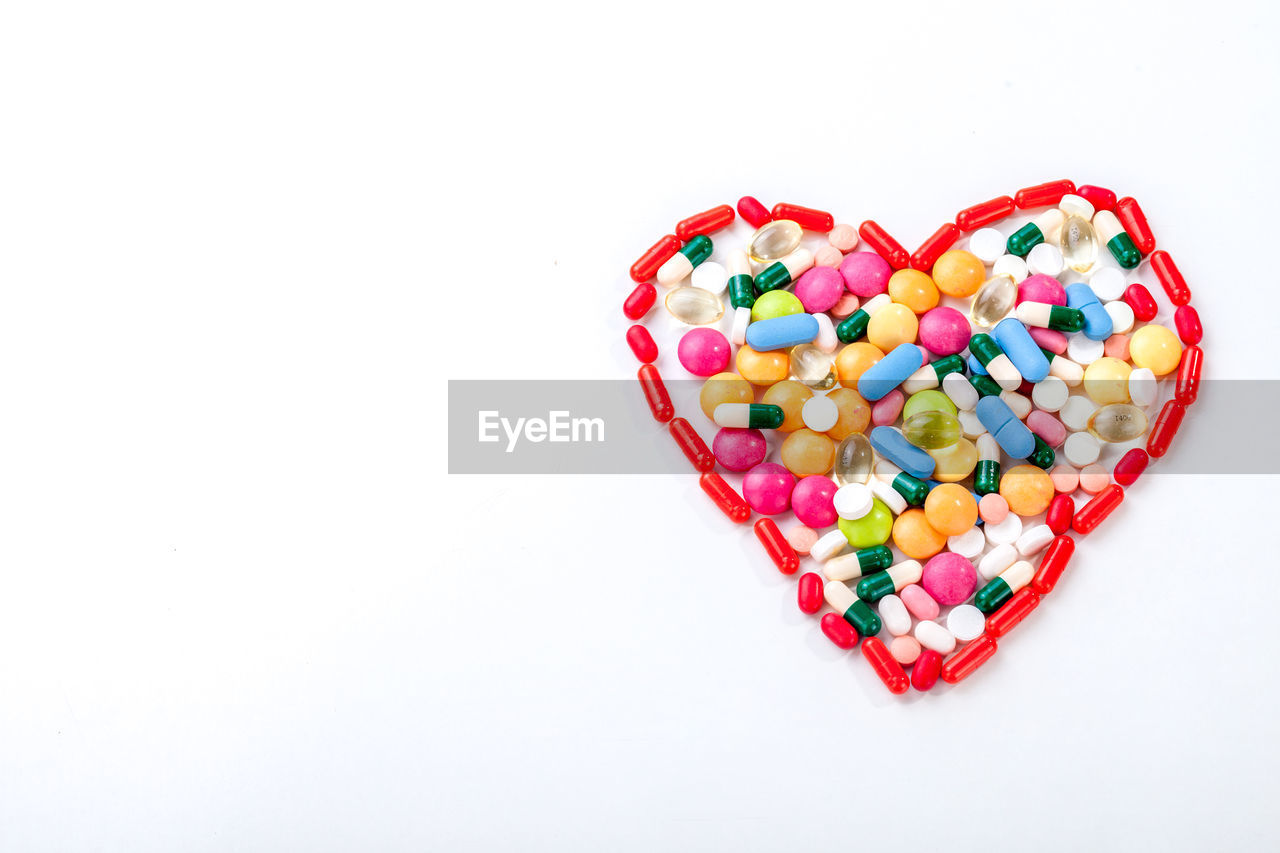 white background, multi colored, studio shot, medicine, pill, healthcare and medicine, heart shape, no people, variation, large group of objects, abundance, candy, sweet food, close-up