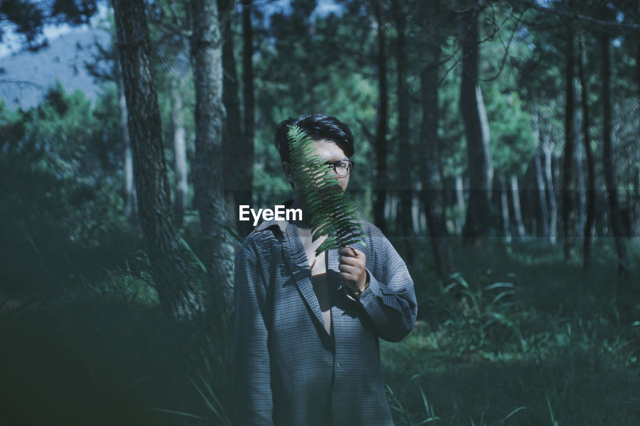 Man With Fern Leaf In Forest