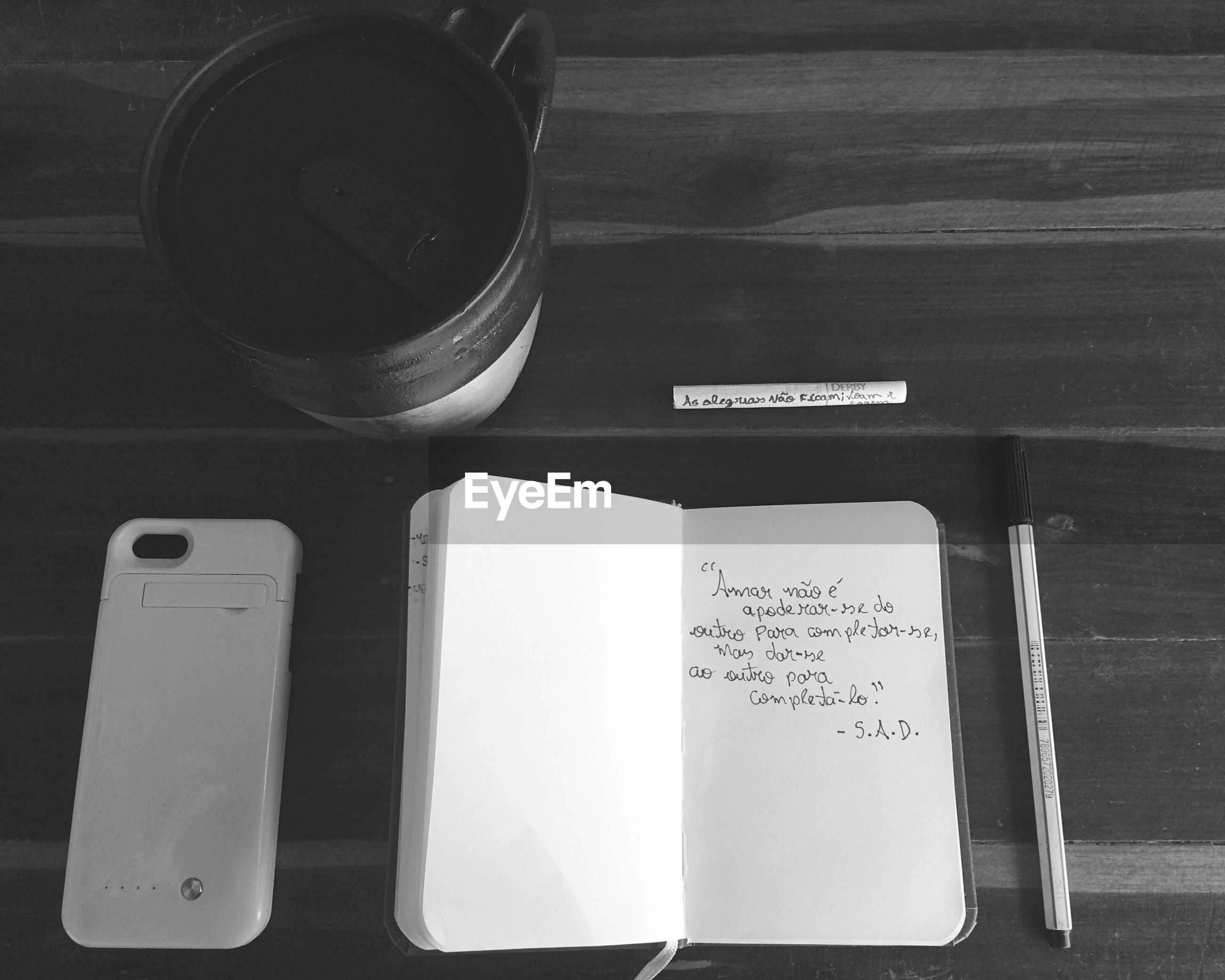 High angle view of notepad with mobile phone and disposable cup on table