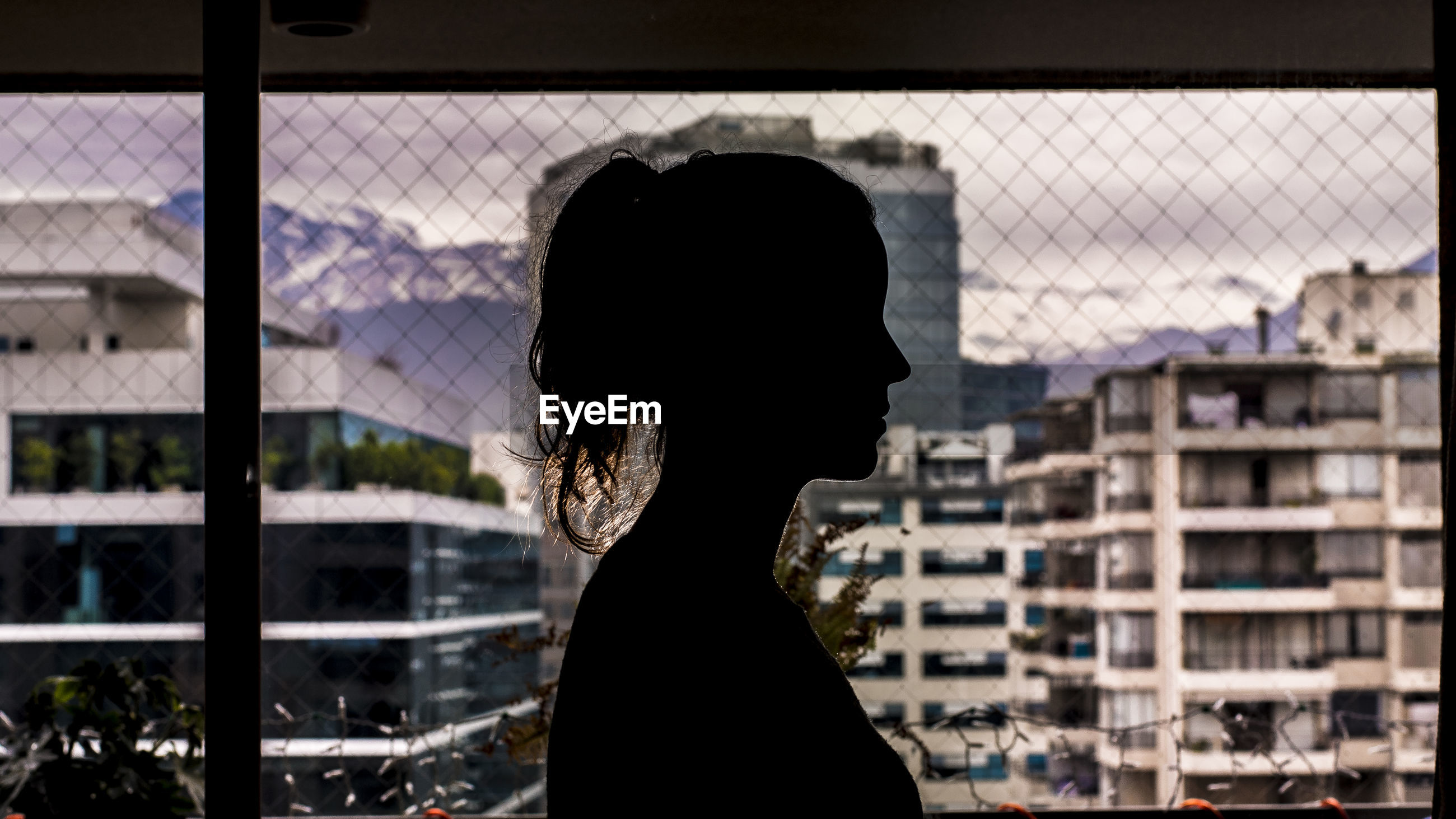 Side view of silhouette woman standing by chainlink fence