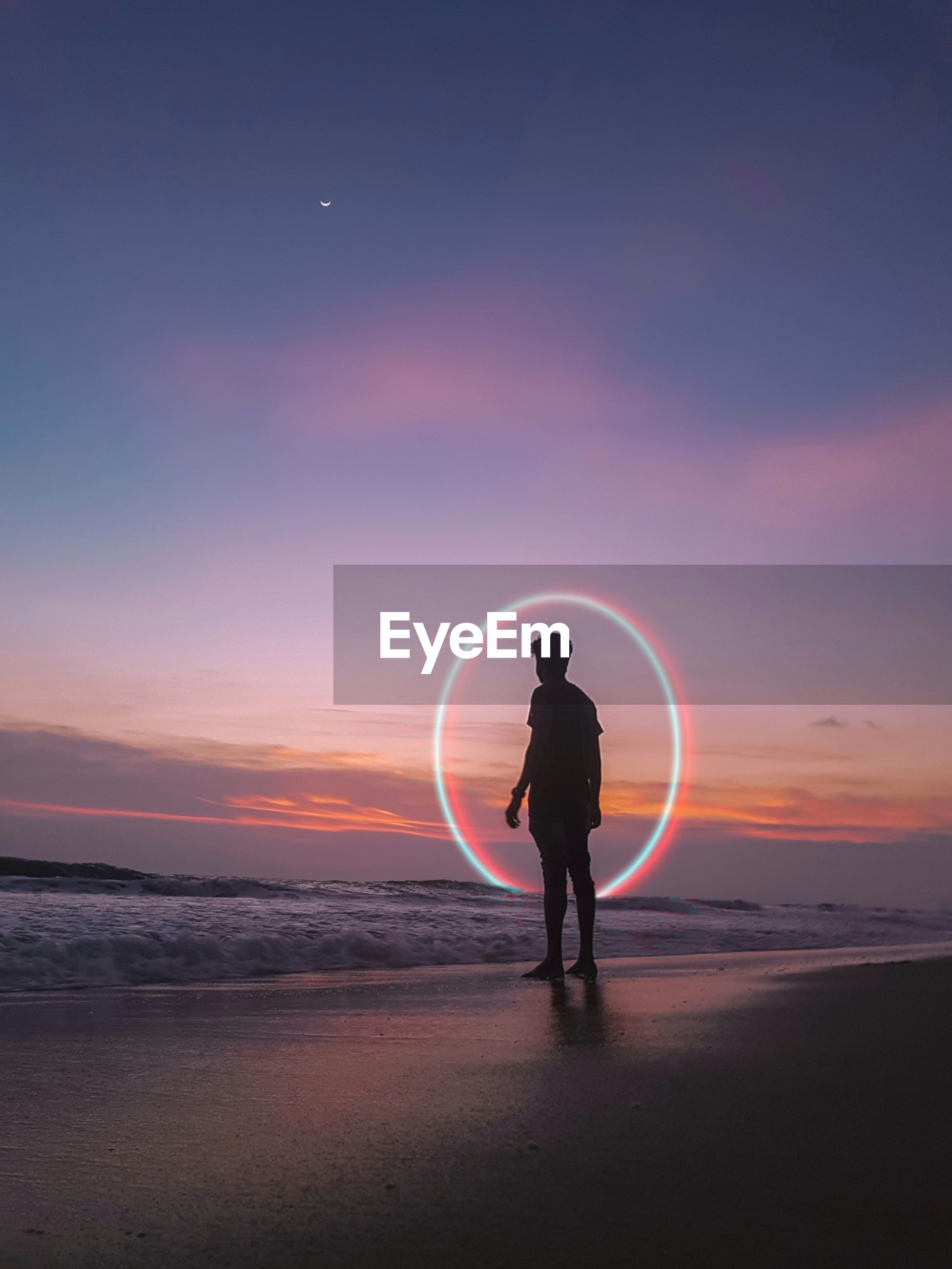 Digital composite image of man standing against circle on beach during sunset