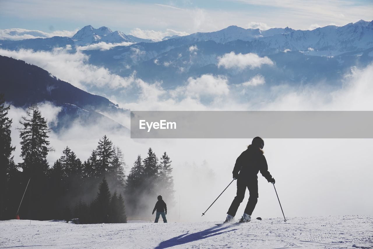 Rear View Of People Skiing On Snow Covered Mountain