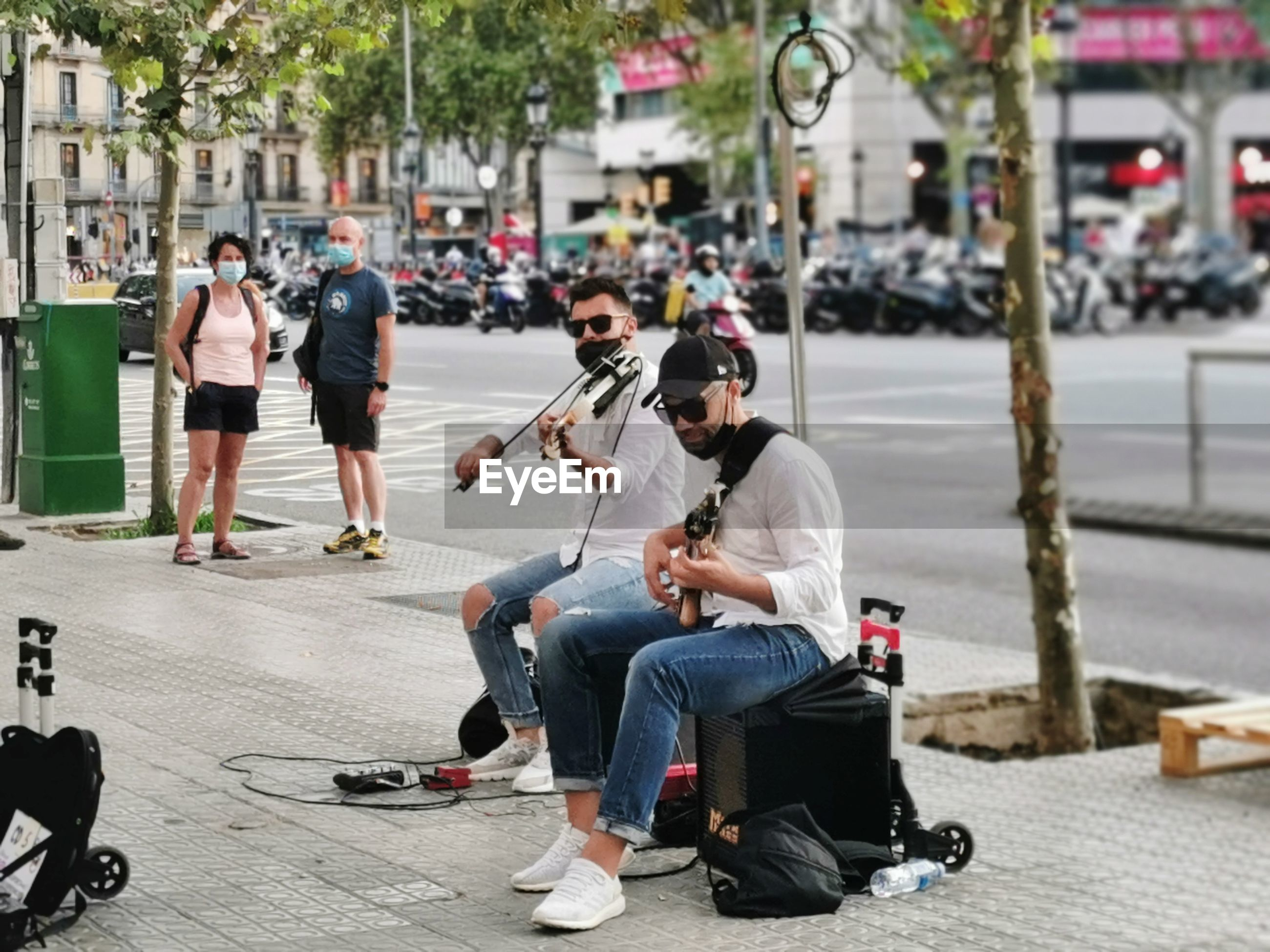 PEOPLE SITTING ON ROAD AGAINST CITY