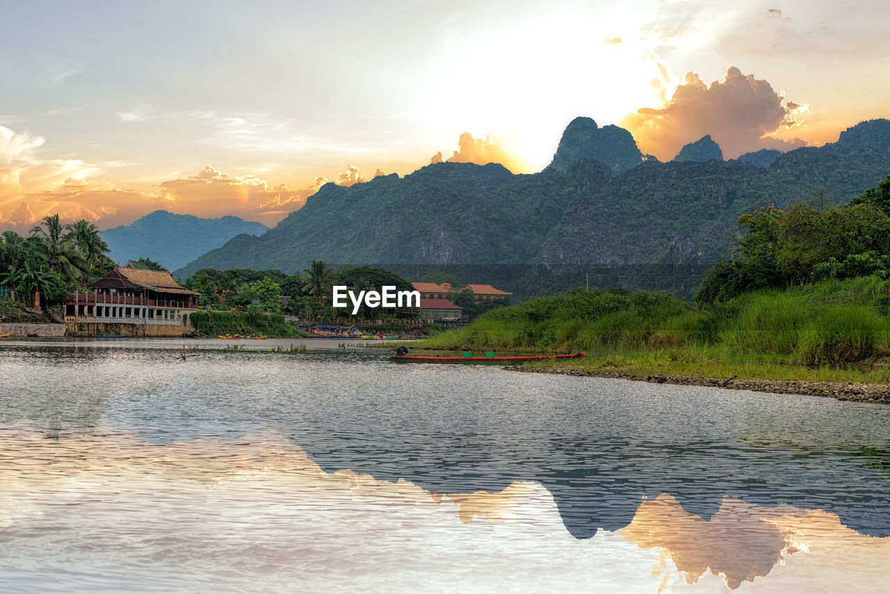 mountain, mountain range, sky, beauty in nature, sunset, nature, scenics, water, river, tranquility, idyllic, no people, tranquil scene, outdoors, cloud - sky, tree, architecture, range, day