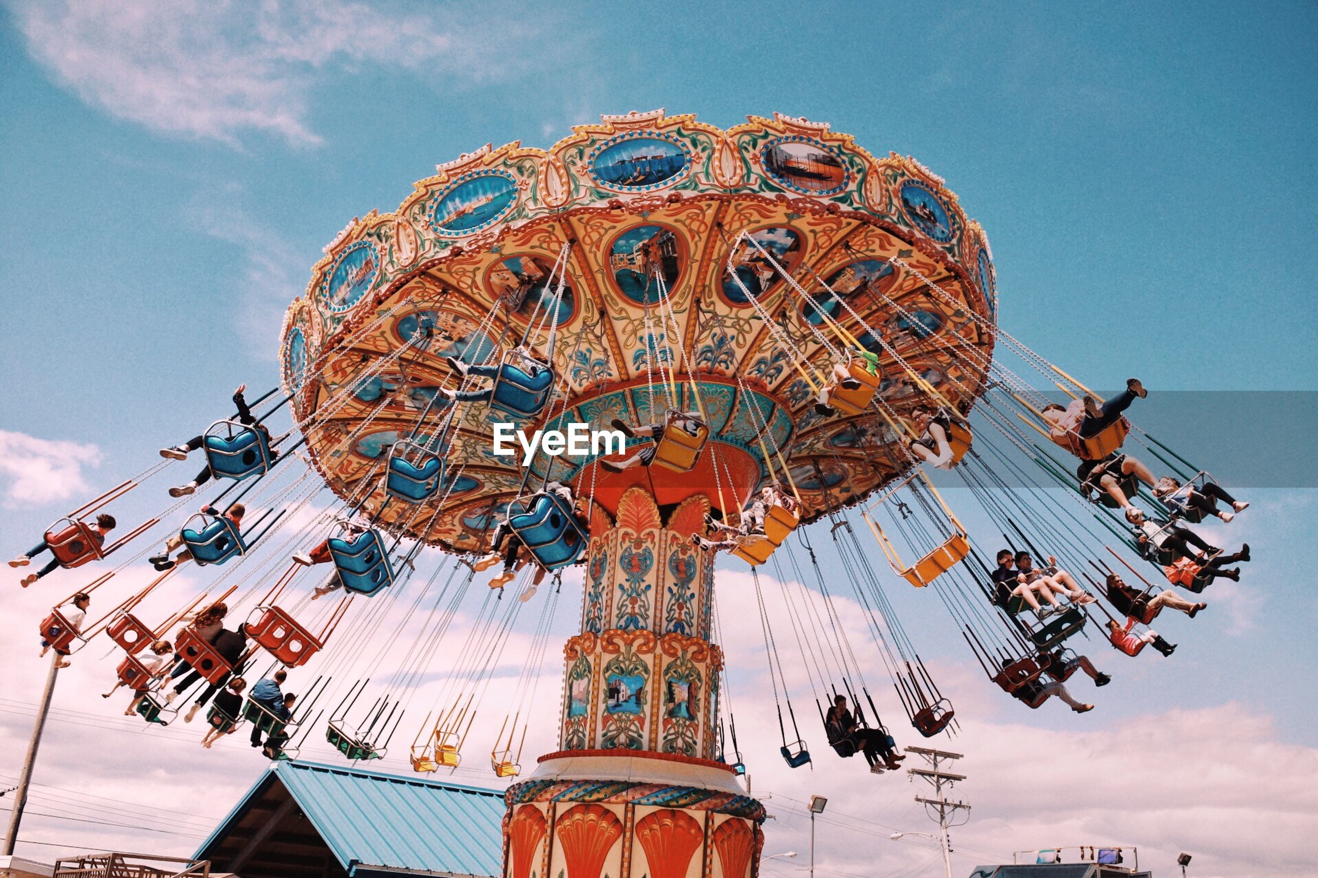 amusement park ride, amusement park, sky, arts culture and entertainment, group of people, chain swing ride, low angle view, nature, real people, leisure activity, cloud - sky, carousel, large group of people, incidental people, day, crowd, architecture, enjoyment, outdoors, built structure, fairground