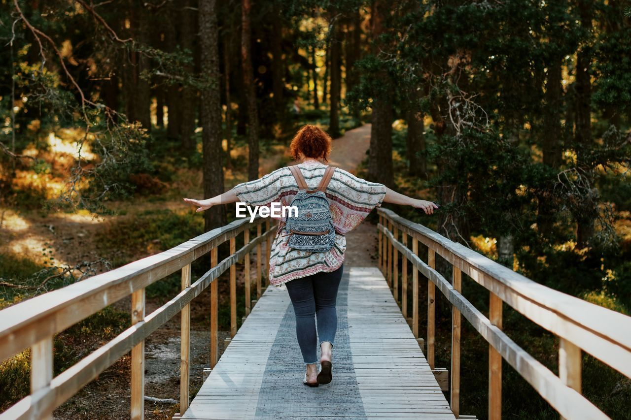Rear view of woman with arms outstretched walking on footbridge in forest