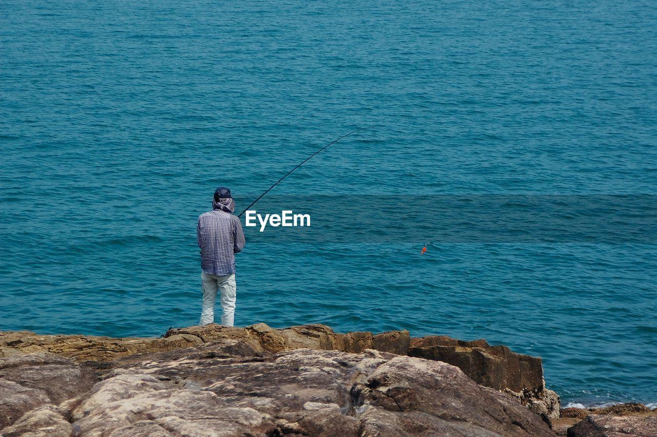 Rear view of man fishing at sea