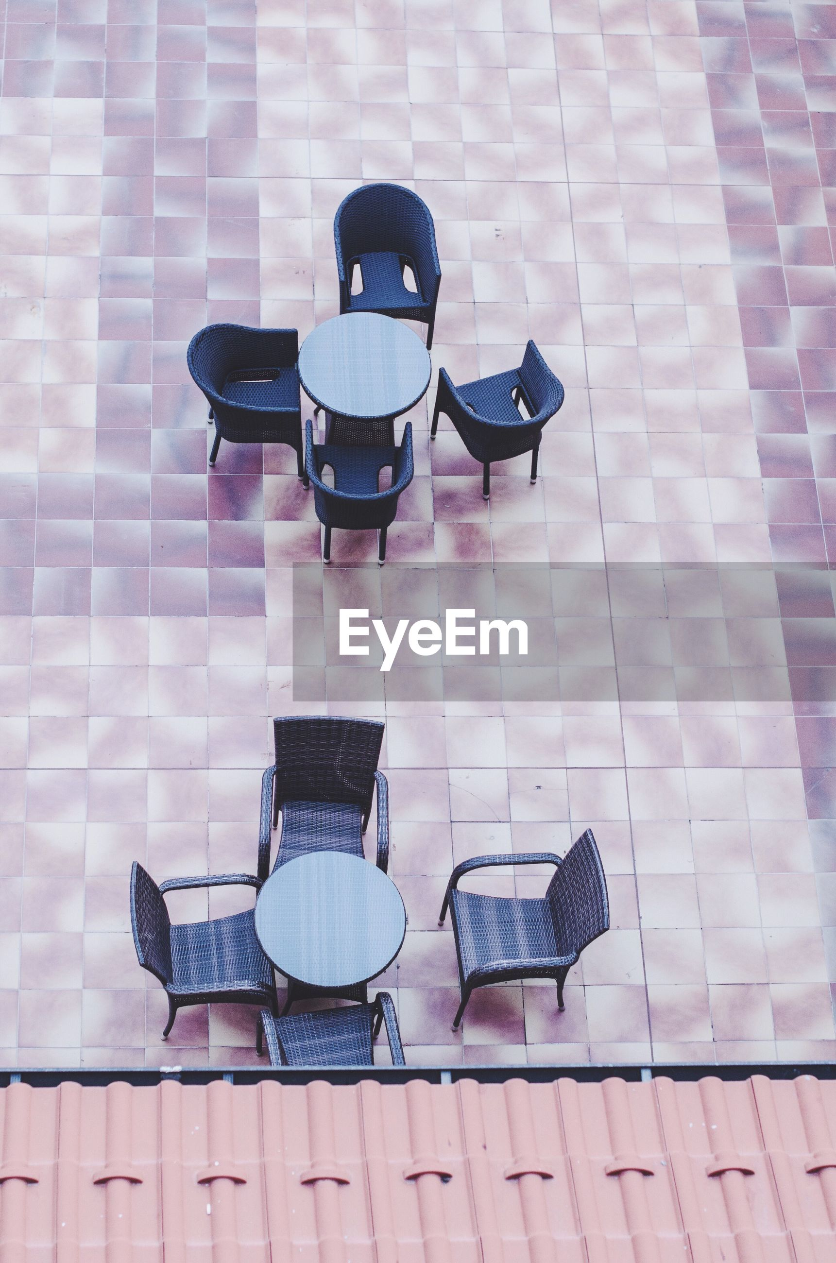 High angle view of tables and chairs arranged in pavement