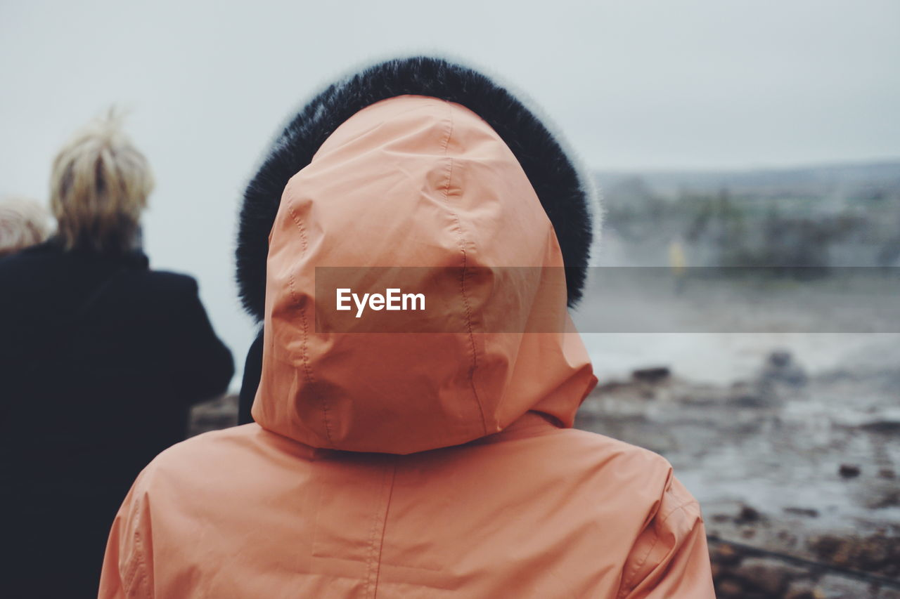 Rear view of people watching geyser