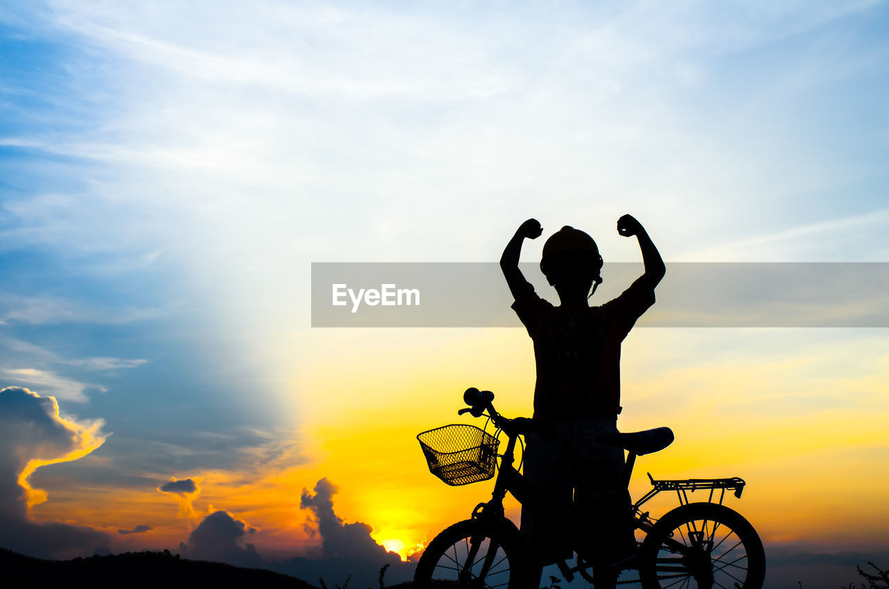 Silhouette Boy With Bicycle Standing Against Sky
