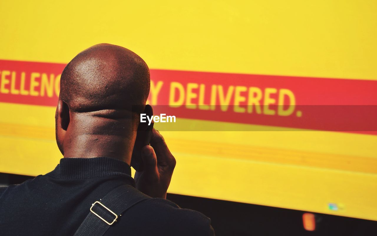Rear view of man with shaved head standing against yellow wall