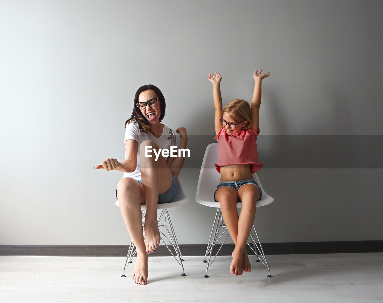 Mother and daughter enjoying against wall at home