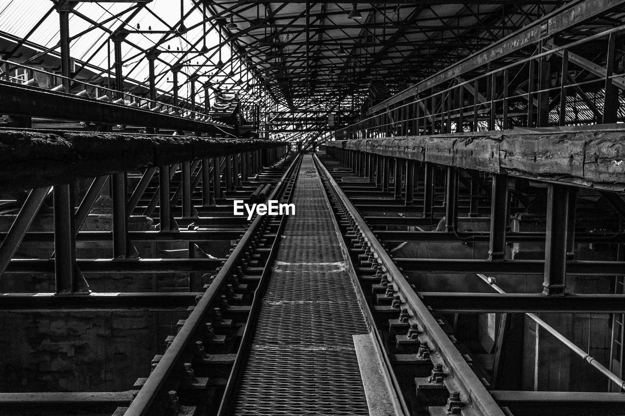 architecture, connection, built structure, rail transportation, metal, diminishing perspective, transportation, bridge, bridge - man made structure, track, railroad track, the way forward, direction, no people, day, railway bridge, outdoors, vanishing point, iron - metal, ceiling