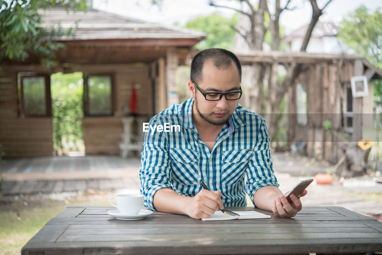 Man With Coffee Cup Using Phone Outdoors