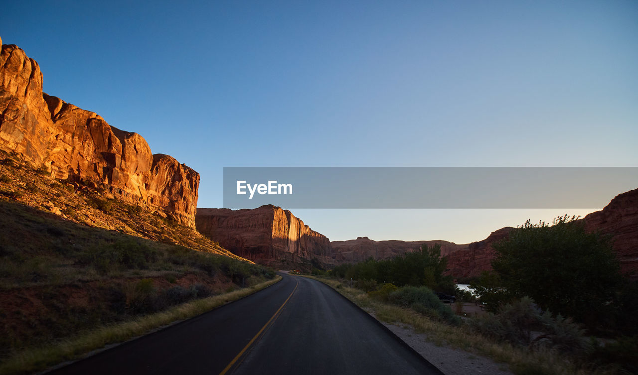 sky, road, the way forward, direction, transportation, mountain, clear sky, nature, beauty in nature, scenics - nature, rock, tranquil scene, tranquility, no people, copy space, non-urban scene, environment, sign, rock - object, symbol, diminishing perspective, mountain range, outdoors, formation