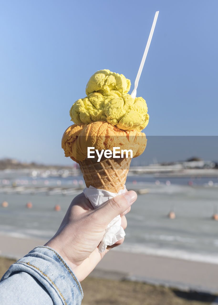 Hand Holding Ice Cream Cone Against Sky