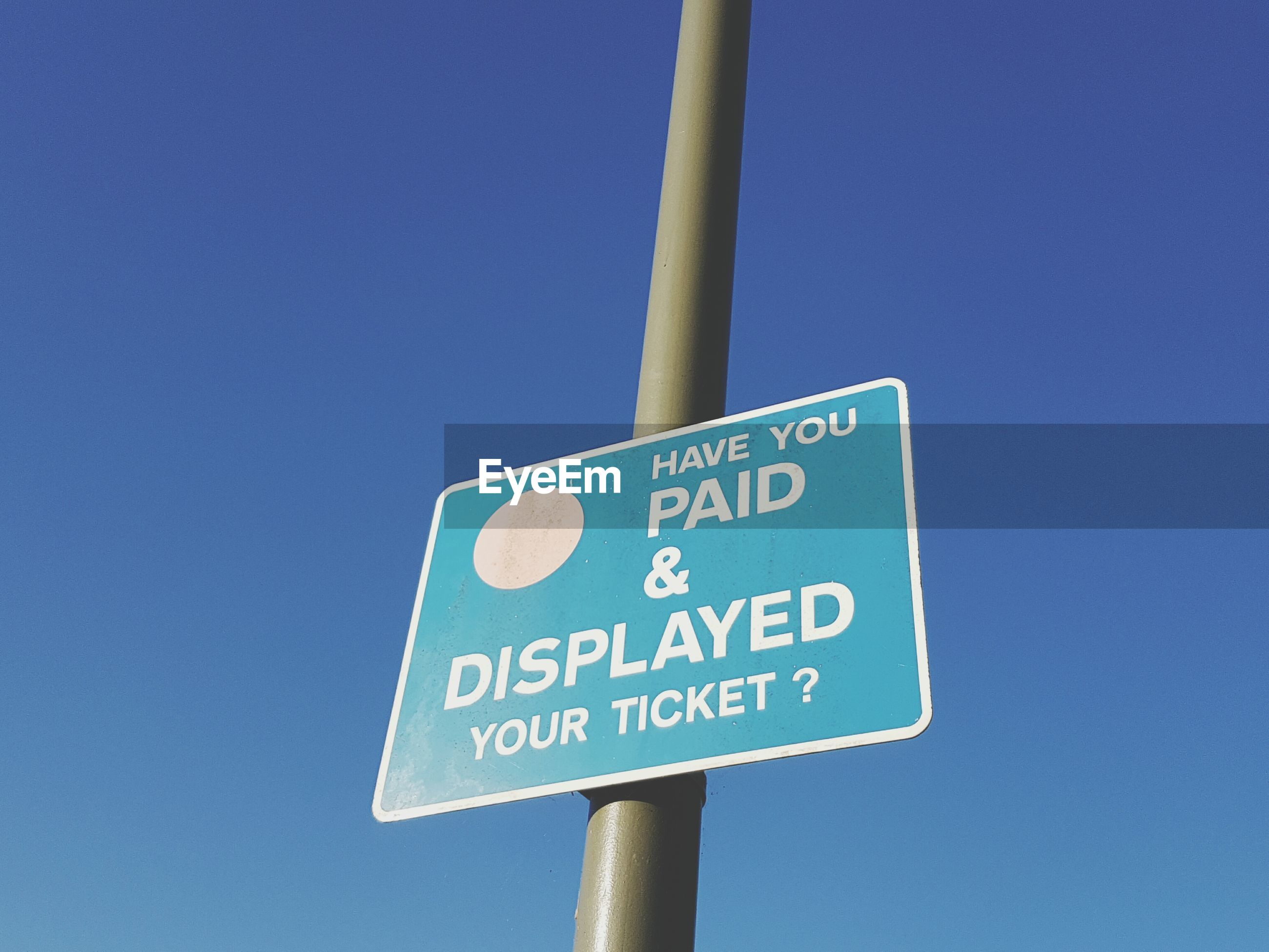 Low angle view of sign board on pole against clear blue sky
