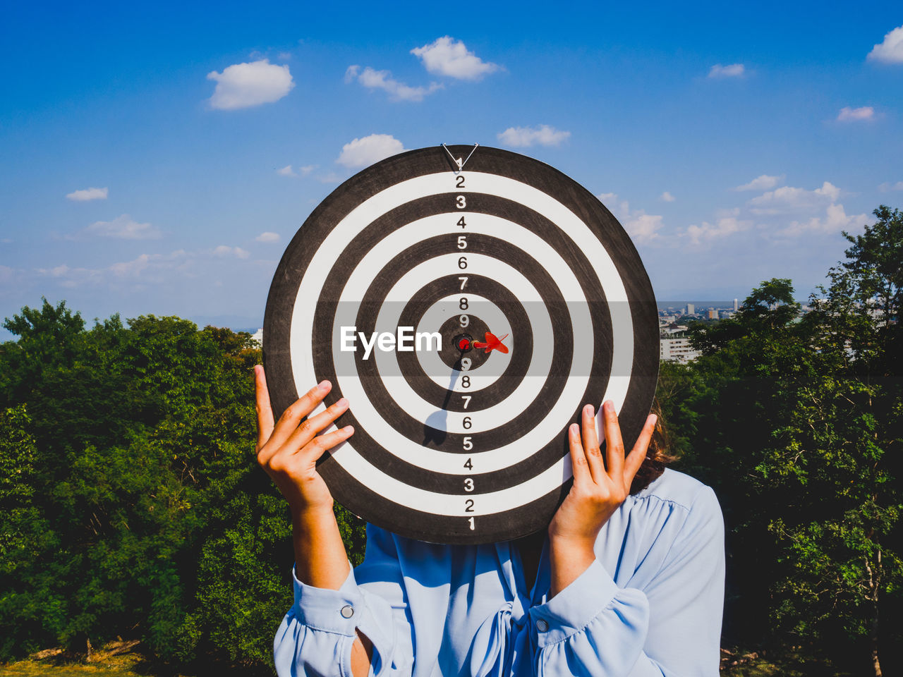 Woman covering face with dartboard against sky