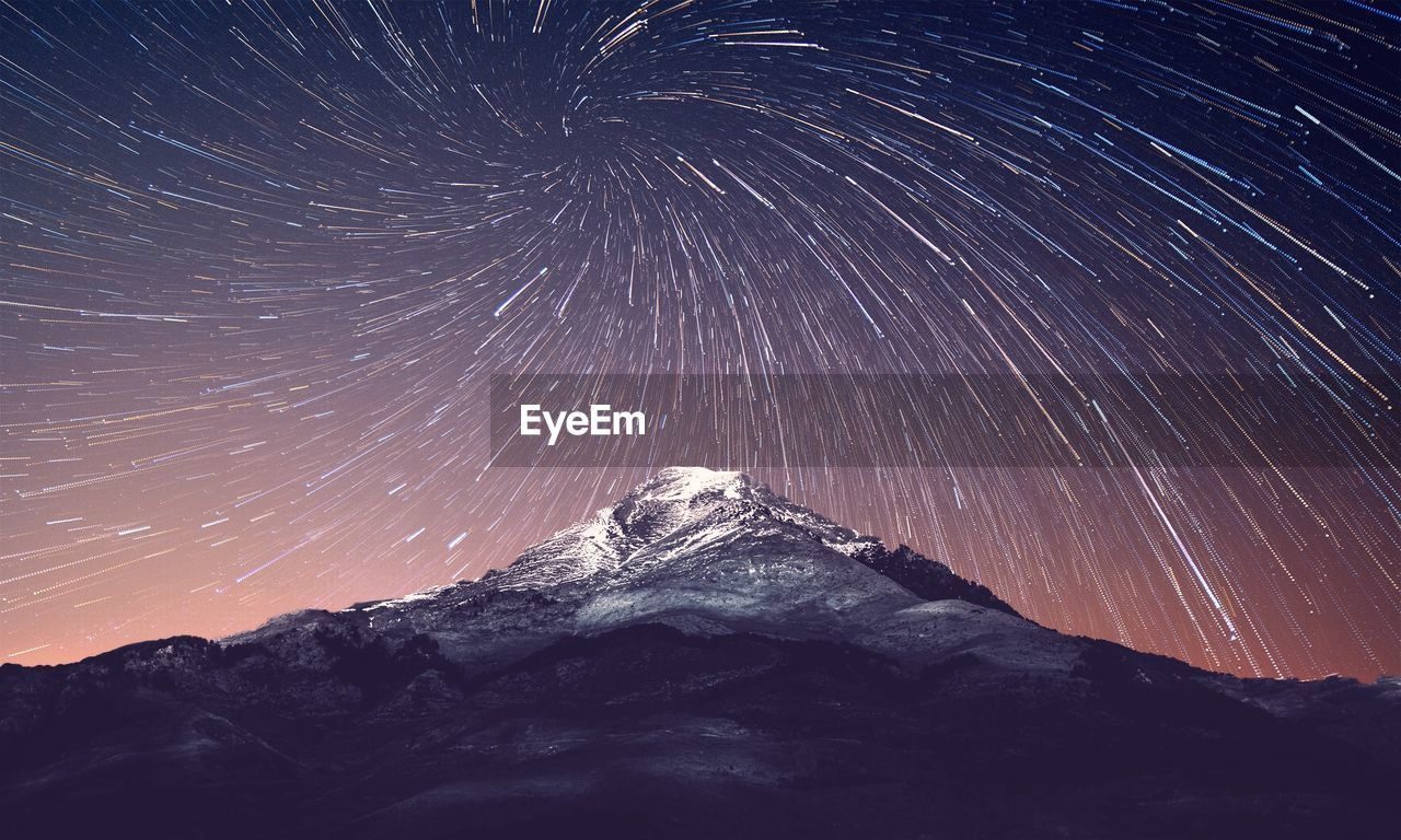 Low Angle View Of Mountain Against Star Trails Against Sky At Night