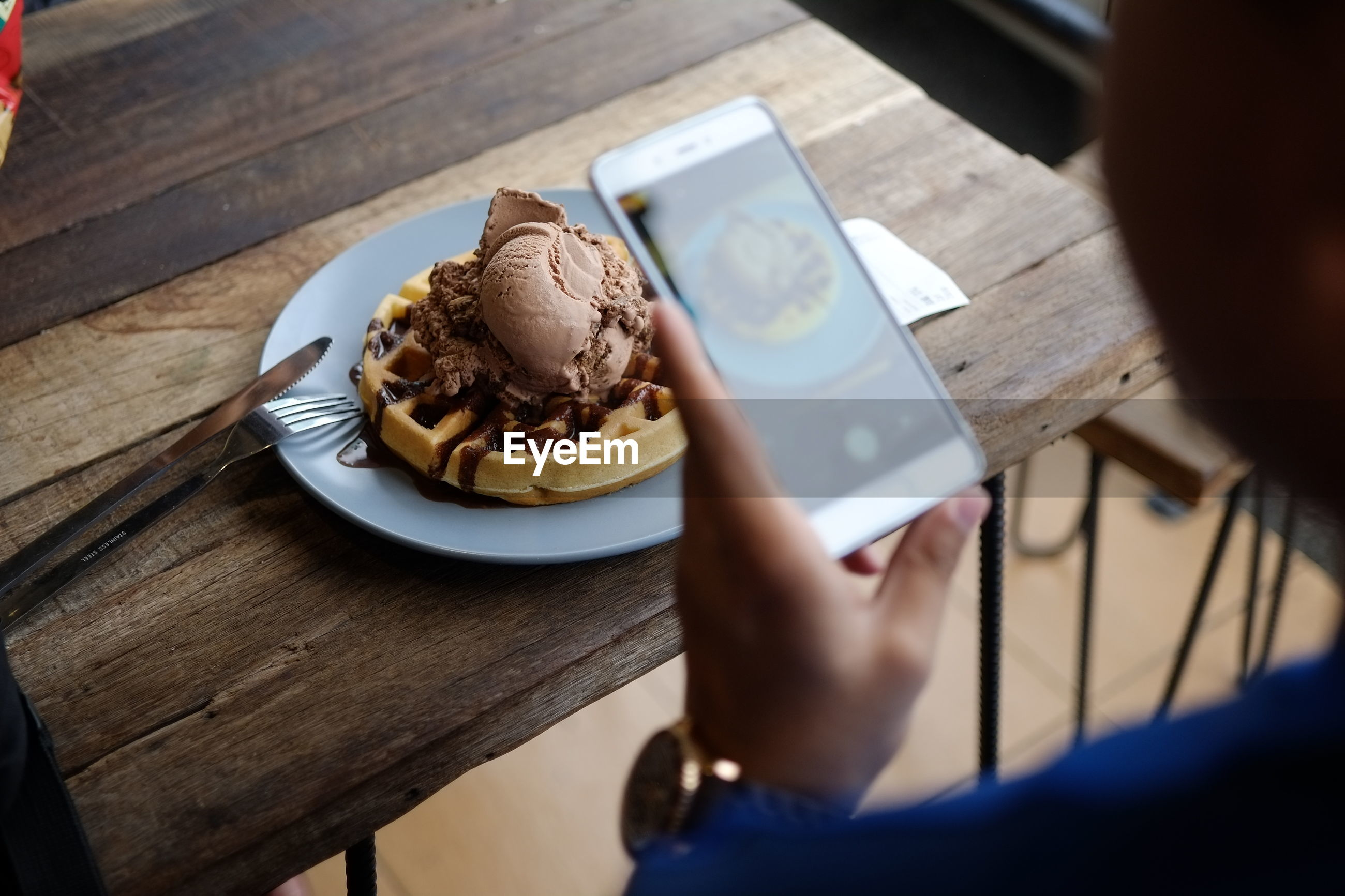Woman photographing food on table