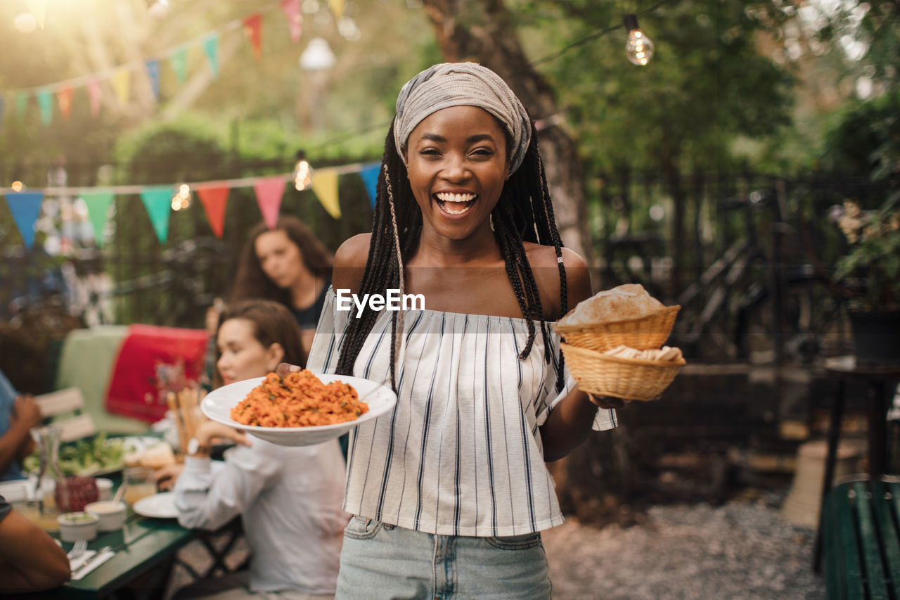 food and drink, food, real people, women, smiling, lifestyles, standing, holding, front view, focus on foreground, portrait, three quarter length, freshness, incidental people, container, looking at camera, adult, people, day, young women, outdoors